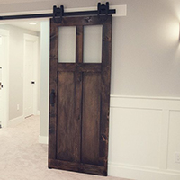 Handmade barn door in the craftsman style with two acrylic glass inserts.